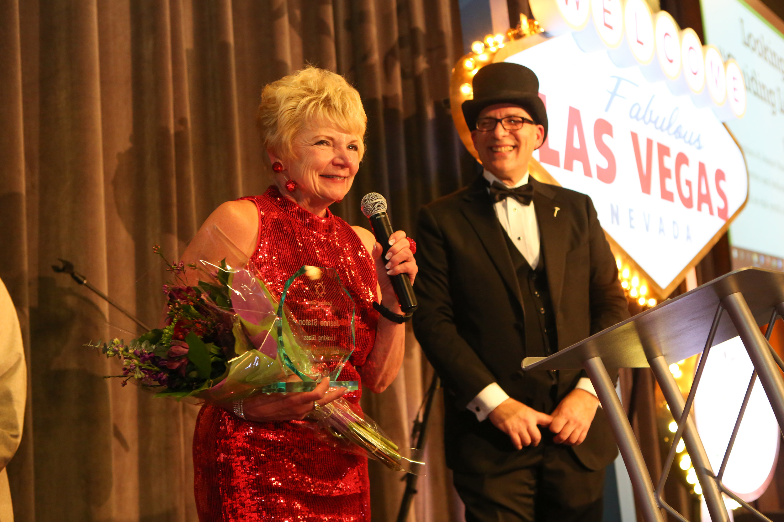"Longtime Looking Glass supporter Jeanne Staton was honored at the auction event with the first ever Looking Glass ""Guiding Light"" award, presented to Jeanne for her years of service and support (auctioneer Larry Snyder smiles in the background)."