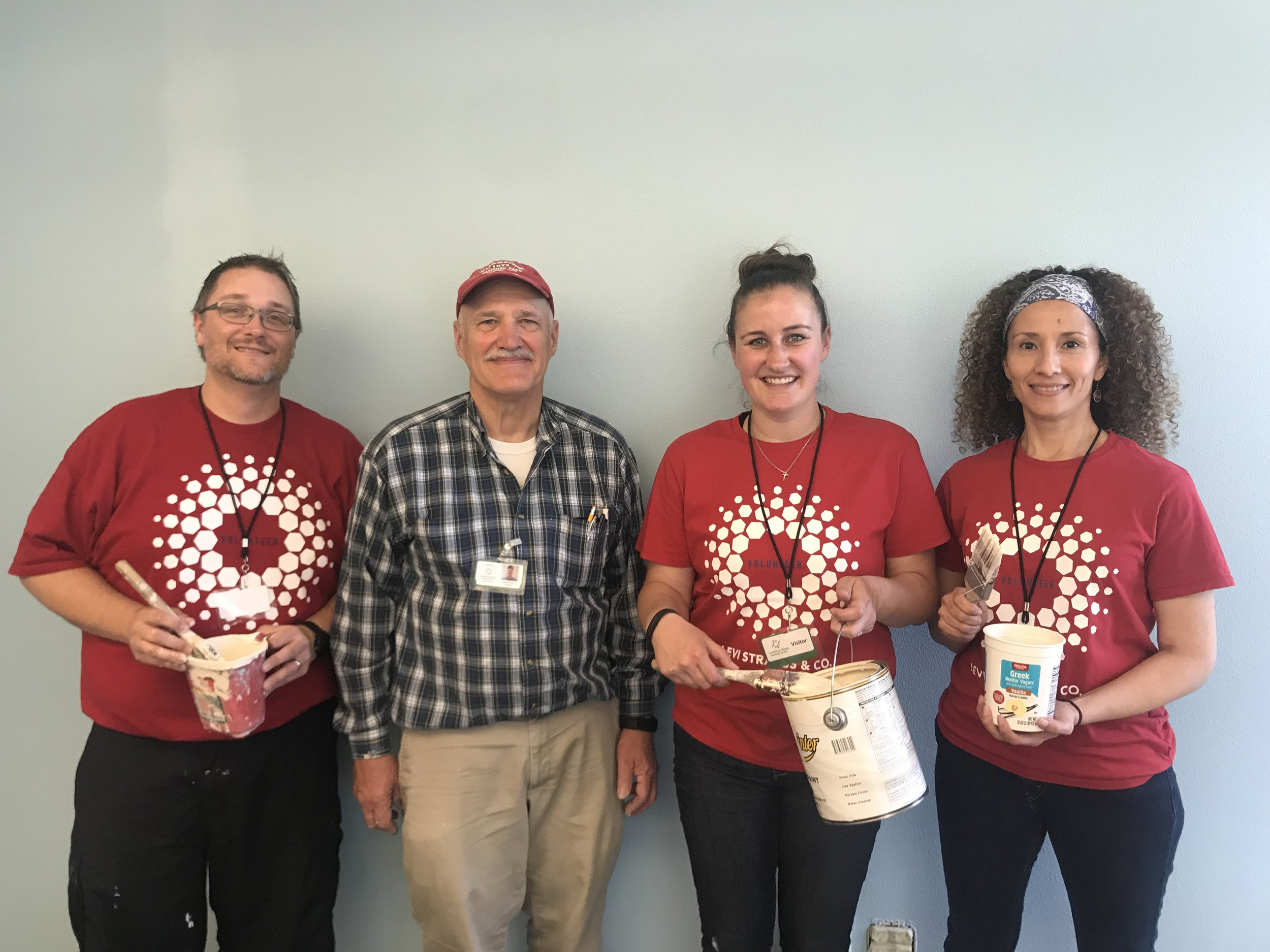 Levi Employees Scott Hanscom, Brianne Emel and Veronica Lockwood join Looking Glass maintenance worker Mike Touchstone in painting a brighter welcoming entrance at the Looking Glass Counseling annex office.