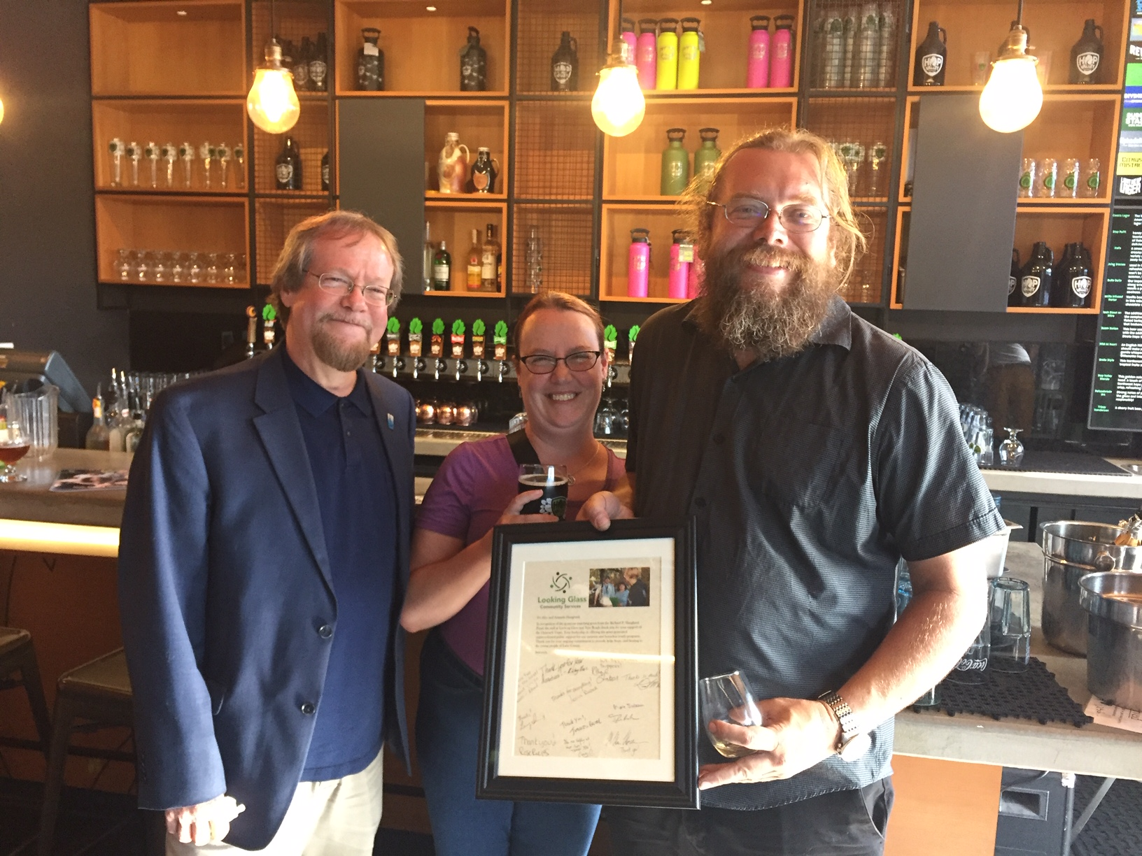 Looking Glass CEO and President Craig Opperman (left) poses with Amy and Alex Haugland after presenting them with a framed thank you letter in appreciation of their support in a $50,000 donation match challenge gift during a celebration gathering at Hop Valley Brewing on Tuesday, July 16th.