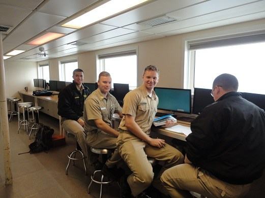 1st Class Cadet Gyle McGurn seen here in the Navigation Lab calculating star time for sights later that night. McGurn is a Lyman Scholarship recipient. Gyle McGurn, a resident of Maui, is seated on far left.