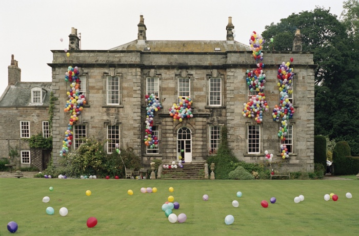 Tim Walker's photograph of balloons pouring out of Eglingham Hall in Northumberland in  Tim Walker Pictures .  (Note that the balloons are floating out of the windows rather than applied to the facade.)