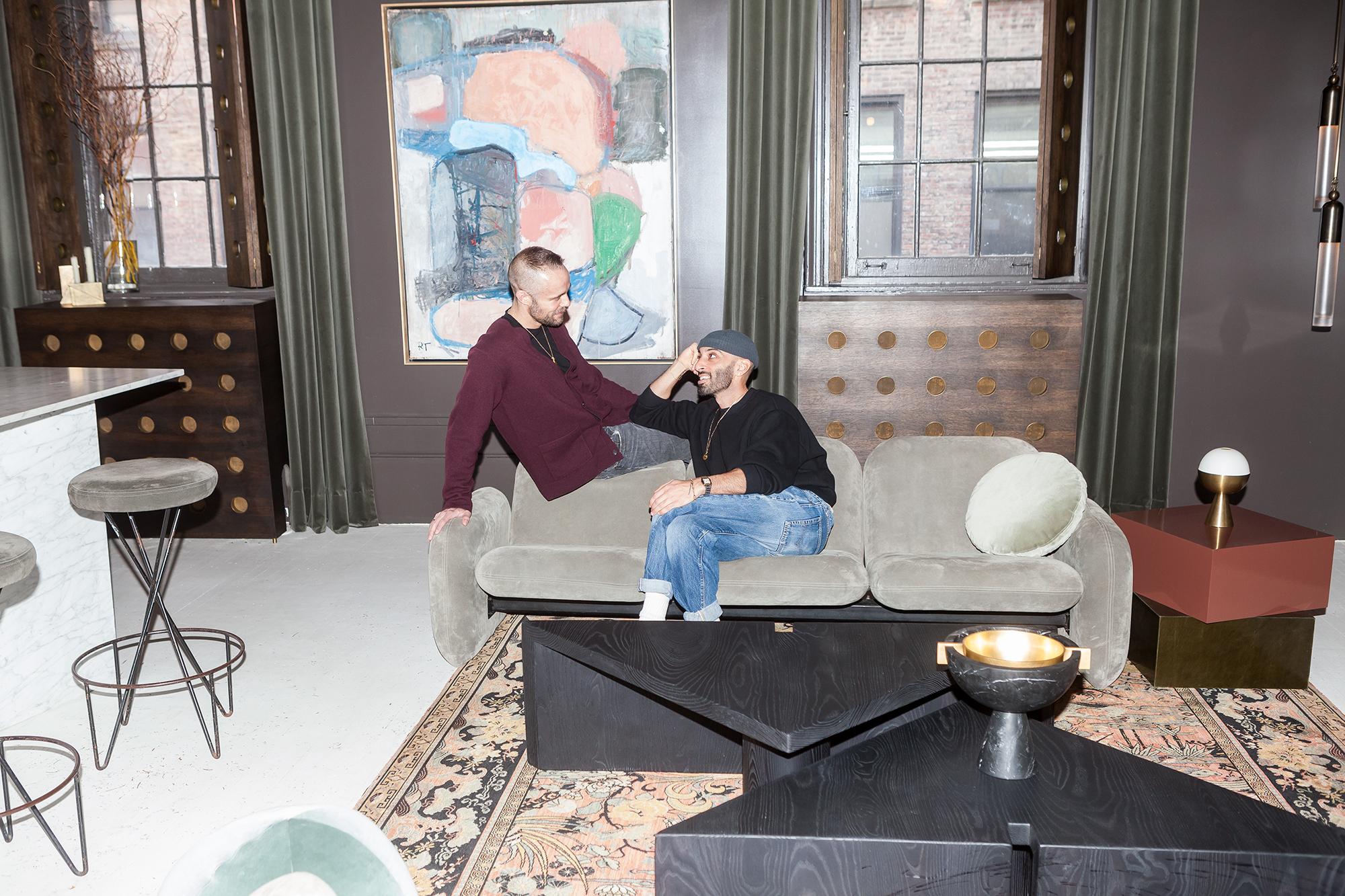 Anderson (left) Hendifar (right) recline on a velvet modernist sofa.