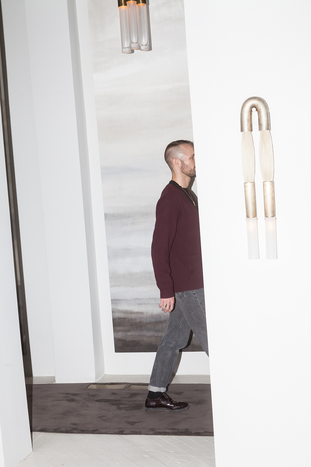 """ABOVE: Anderson takes a stroll through the palatial Apparatus headquarters. OPPOSITE: A carpeted hallway featuring one the brand's now-iconic """"Cloud"""" chandeliers."""