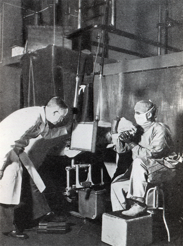 Dr. Clerf holding head, Dr. Hodes looking in fluoroscope