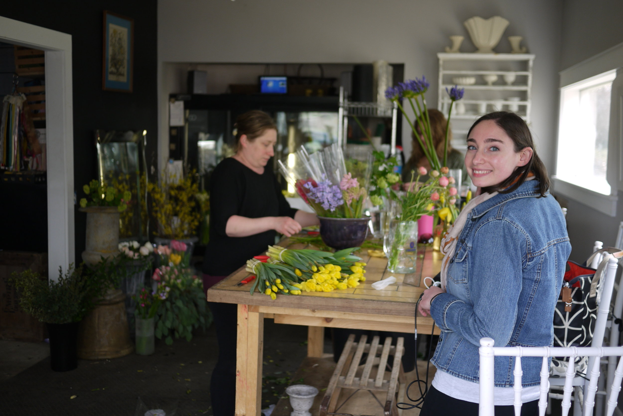 Producer Molly Donahue looks on as Emily & Emma work on a shipment of flowers.