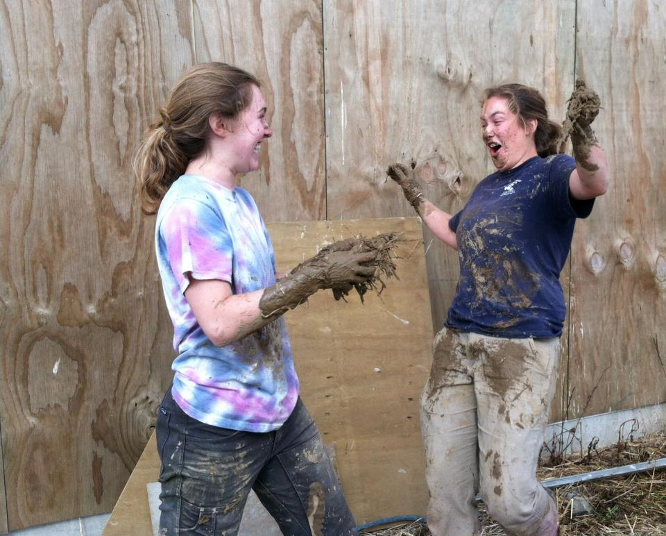 Shea and her friend having some fun with mud on the farm.