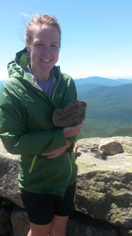 Kelsey Barklund on Mount Lafayette in New Hampshire, posing with the first memorial stone she made for her grandfather John.