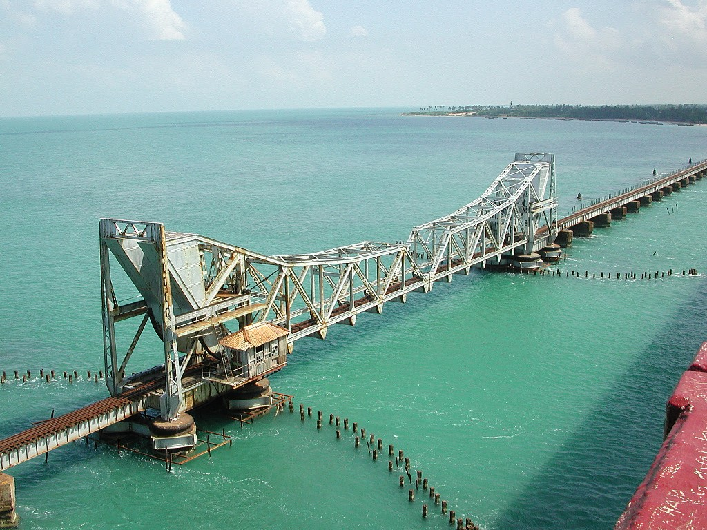 The Pamban Bridge is a railway bridge on the Palk Strait which connects the town of Rameswaram on Pamban Island to mainland India. The bridge refers to both the road bridge and the cantilever railway bridge, though primarily it means the latter. Opened on 24 February 1914, it was India's first sea bridge, and was the longest sea bridge in India until the opening of the Bandra-Worli Sea Link in 2010. The rail bridge is, for the most part, a conventional bridge resting on concrete piers, but has a double leaf bascule section midway, which can be raised to let ships and barges pass through.