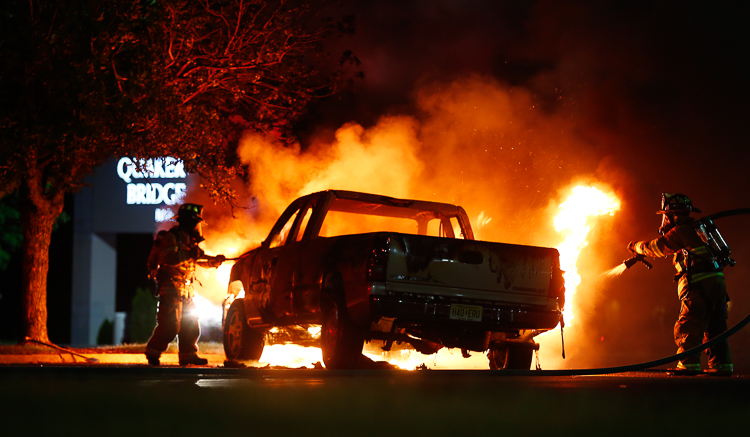 Firefighters with the Slackwood Volunteer Fire Co. in Lawrence Township, work quickly to put out a fire which fully engulfed a pickup truck in the parking lot of Quaker Bridge Mall. Lawrence Township, NJ  6/12/15   (Photo Credit: Saed Hindash)