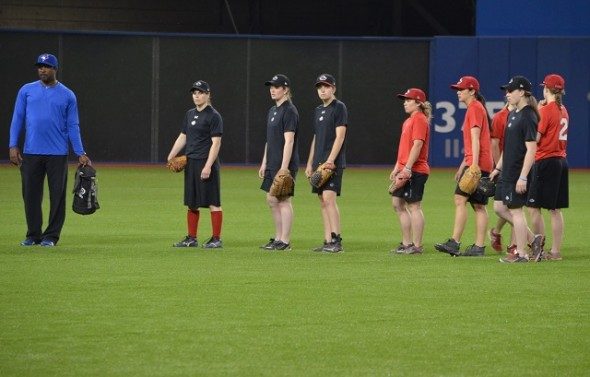 Canada's women team began preparing for the Pan Am Games competition next month in Ajax with an intra-squad game at the Rogers Centre on Monday. Outfielders, like Autumn Mills (first in line in red) were given pointers by former Gold Glove winner Devon White. Photo: Alexis Brudnicki