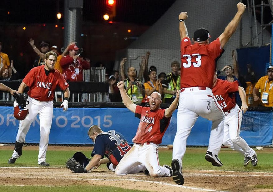 The moment was golden: Peter Orr slides home with the game winner in extras against Team USA as 1B coach Larry Walker throws his arms into the air. Photo: Joseph Howarth.   For more.