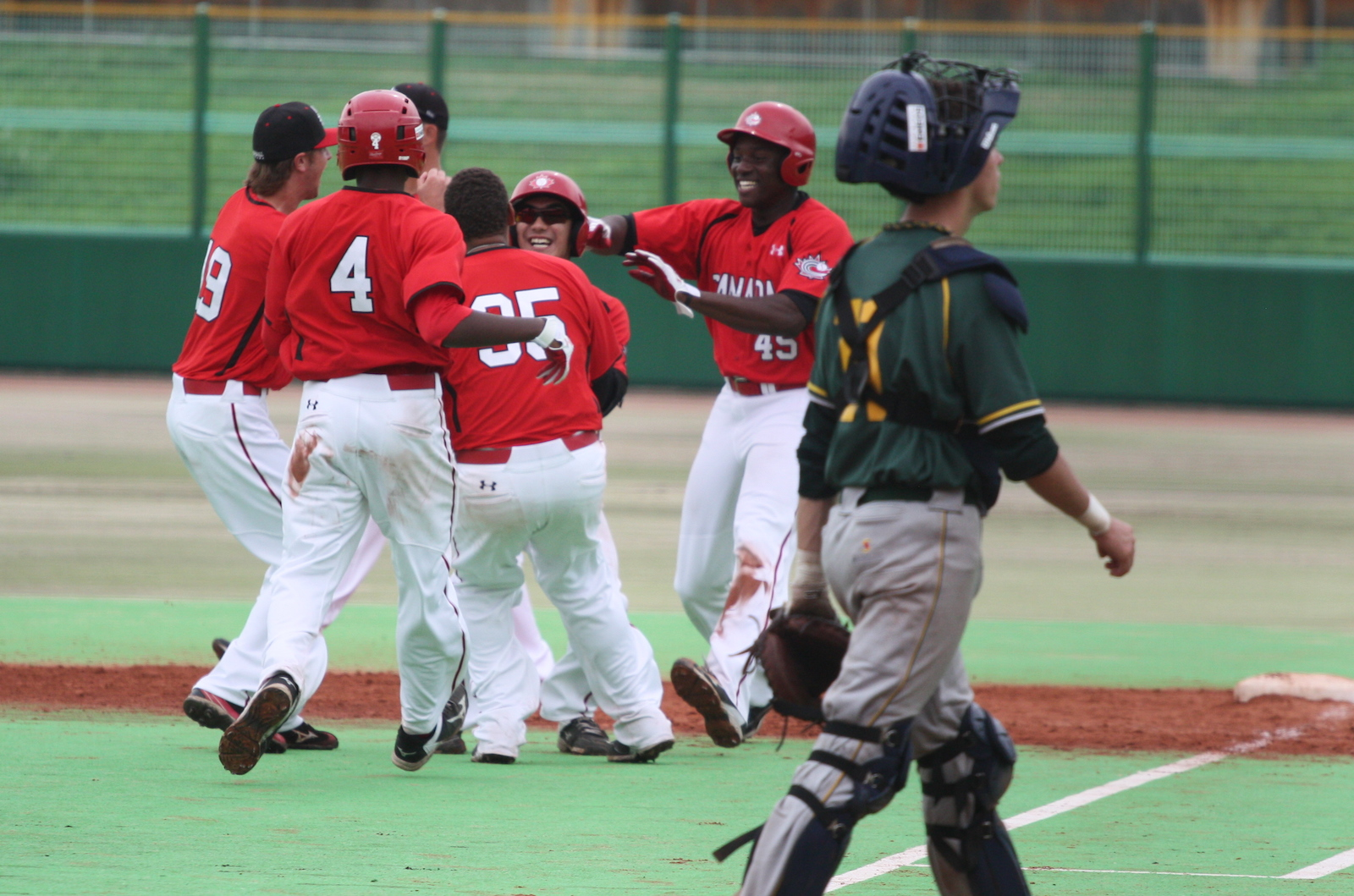 Canadian teammates mob Royce Ando (Mississauga, Ont.) after his walk-off single against South Africa.