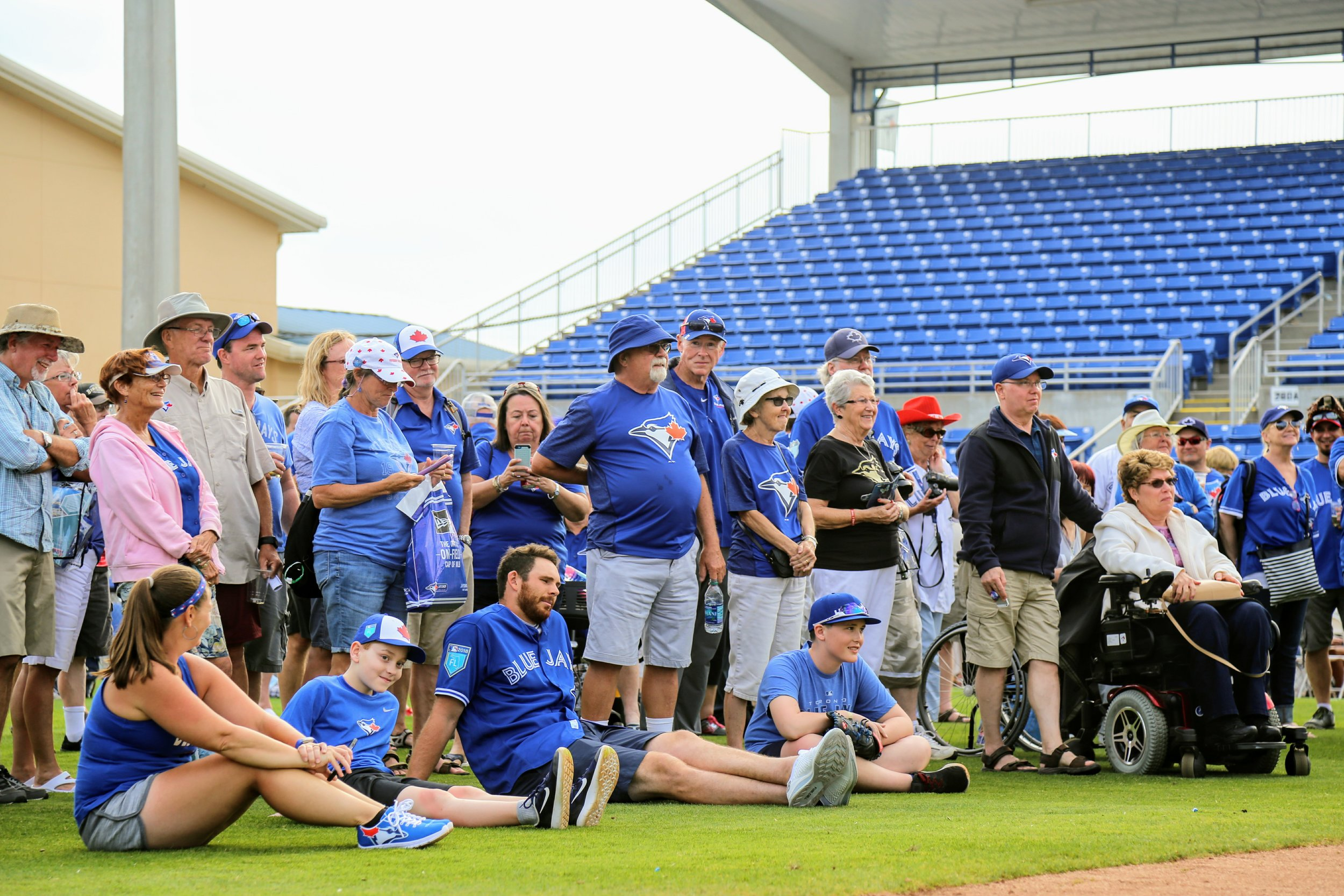 Blue Jays right-hander Joe Biagini (middle on ground) takes a seat among the club's season ticketholders at an event at Dunedin Stadium on Tuesday.
