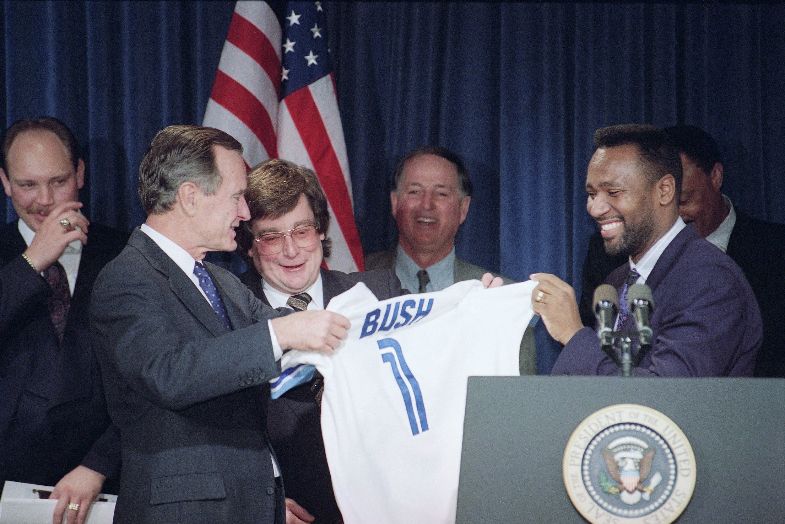 President George H. W. Bush, left, accepts a Toronto Blue Jays Jersey from Jays Joe Carter, right, during a ceremony honoring the World Serres champs at the White House, Dec. 16, 1992, Washington, D.C. Blue Jays RP Duane Ward, from left, President Paul Beston (Welland, Ont.),, General Manager Pat Gillick and manager Cito Gaston look on. Phhoto: Ron Edmonds/AP Photo.