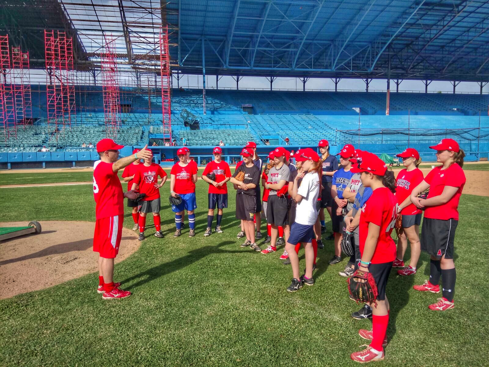 Andre Lachance (far left) talks to young Canadian players attending the national women's team development camp in Cuba