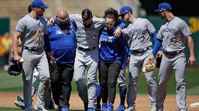 RHP Matt Shoemaker, third from left, is helped off the field by the Blue Jays medical staff and others after tearing his AC.