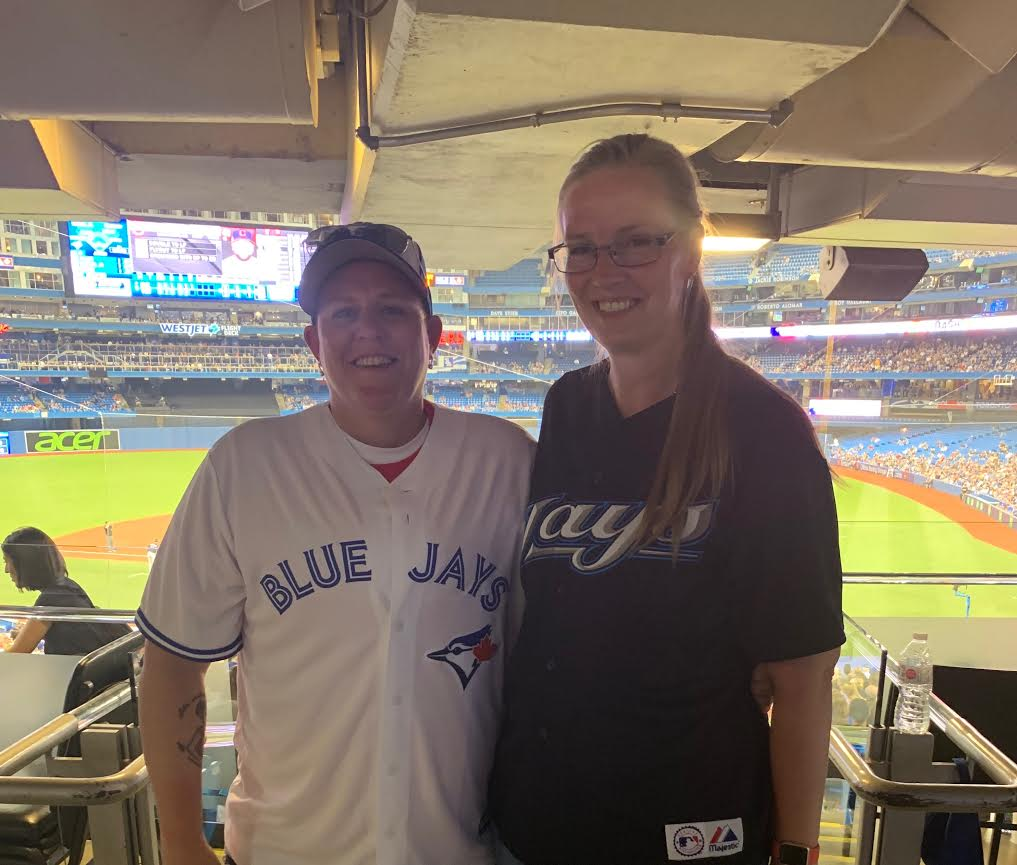 Merinda Halladay, older sister of Roy Halladay, right, and her wife Kelly … two of the seven Halladay members who were at Cooperstown Sunday and caught the Blue Jays loss Monday at the Rogers Centre to the Cleveland Indians.