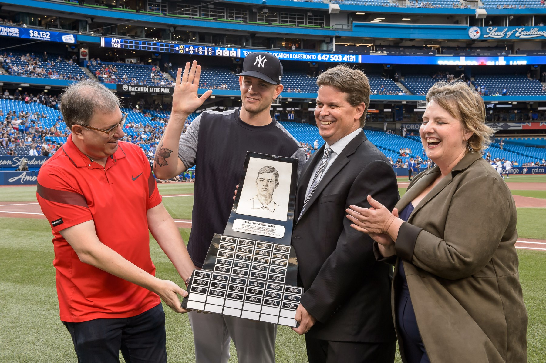 Ladner, B.C., native James Paxton (second from left) was presented with the Canadian Baseball Hall of Fame's 2018 Tip O'Neill Award in a pre-game ceremony at the Rogers Centre on Friday. Canadian Baseball Hall of Fame board member Mike Wilner (left), Hall director of operations, Scott Crawford (second from right) and Hall board member Tammy Adkin were on hand for the presentation. Photo: Toronto Blue Jays/Canadian Baseball Hall of Fame