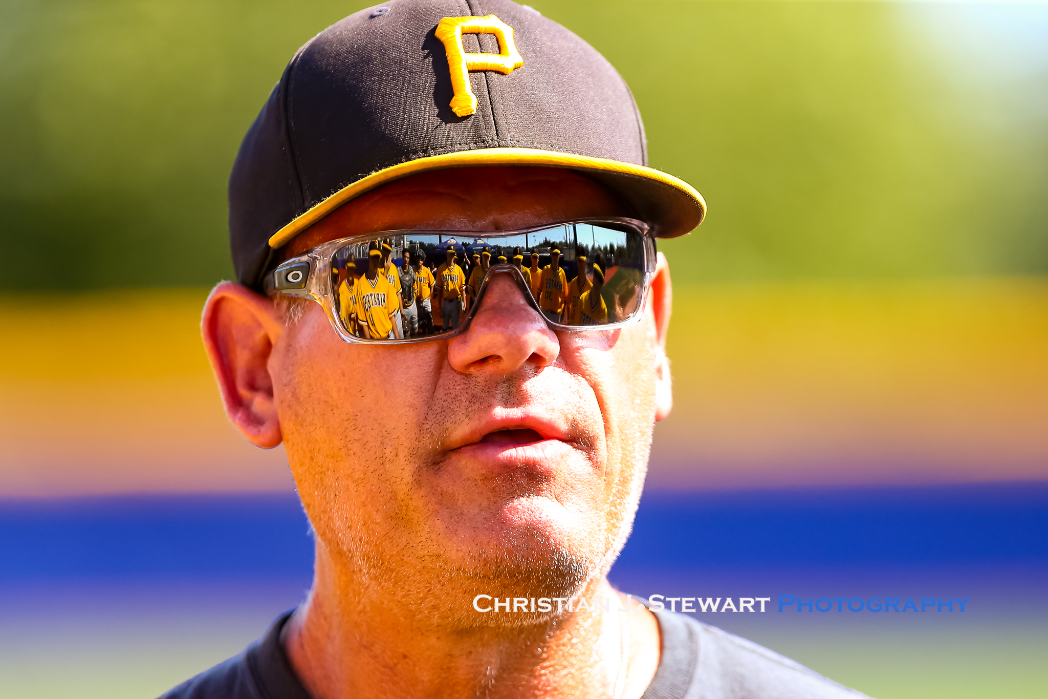 With his team reflected in his sunglasses, Pirates Head Coach Doug Rogers delivers some motivation late in Sunday's game. Photo: Christian J. Stewart.