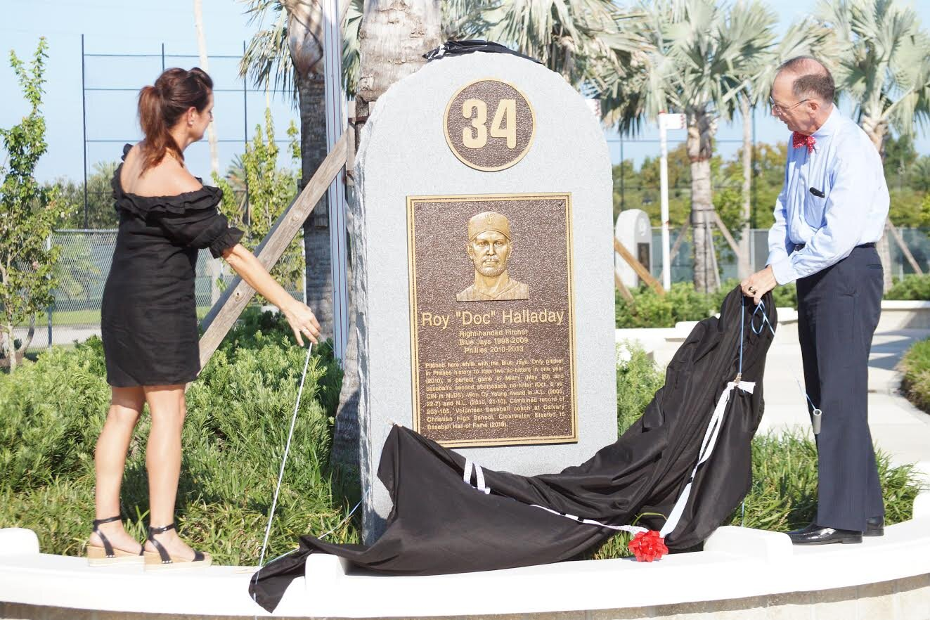 Brandy Halladay, left, and Clearwater Mayor George Cretekos unveil the memorial monument to Brandy's late husband Roy Halladay at Jack Russell Memorial Stadium in Clearwater, Fla. Photos; Eddie Michels.