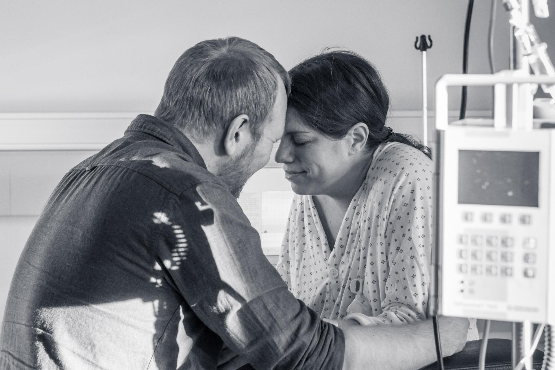 Mann støtter sin fødende kone under fødselen