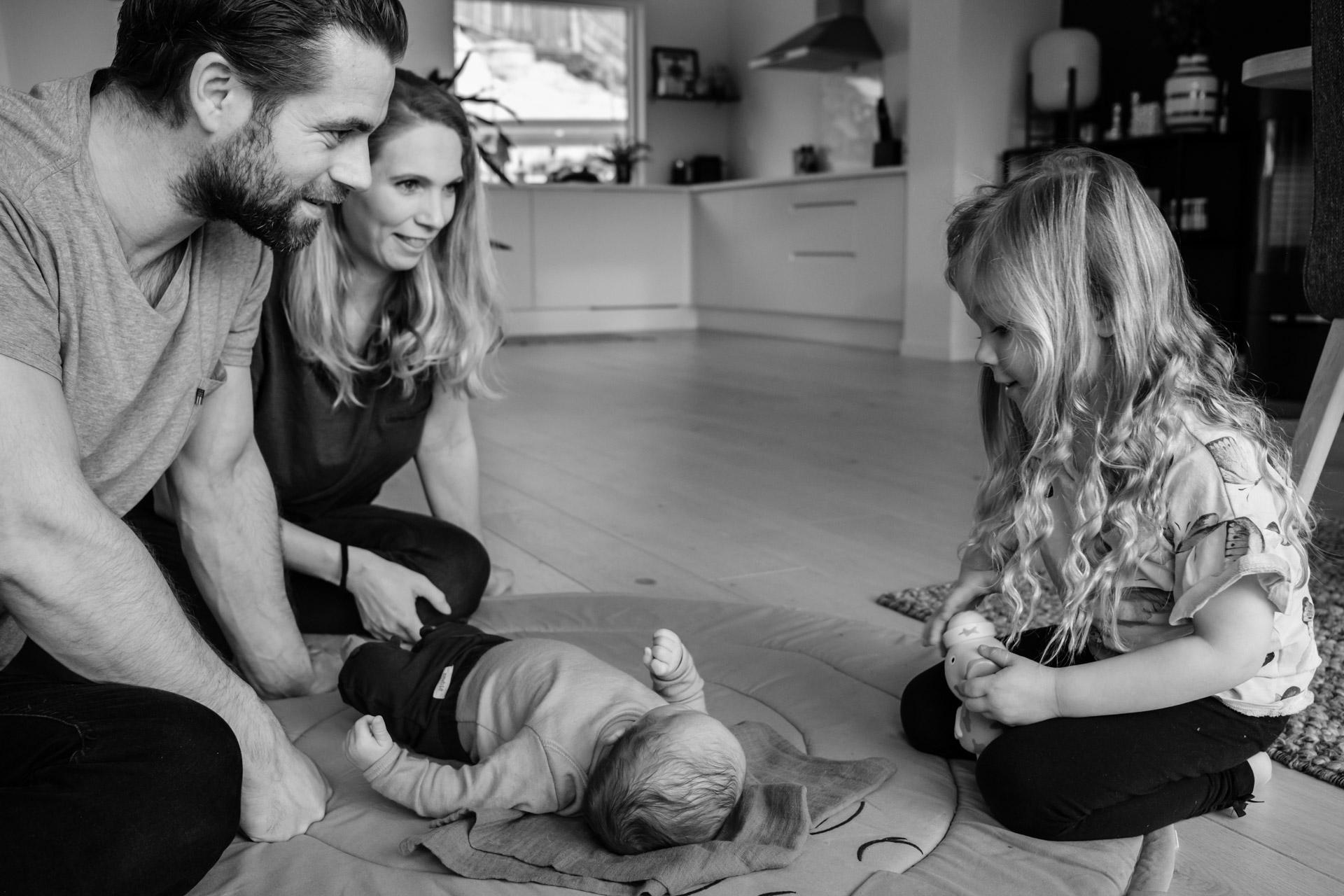 Foreldre og storesøster sitter på gulvet hvor nyfødt baby ligger.jpg