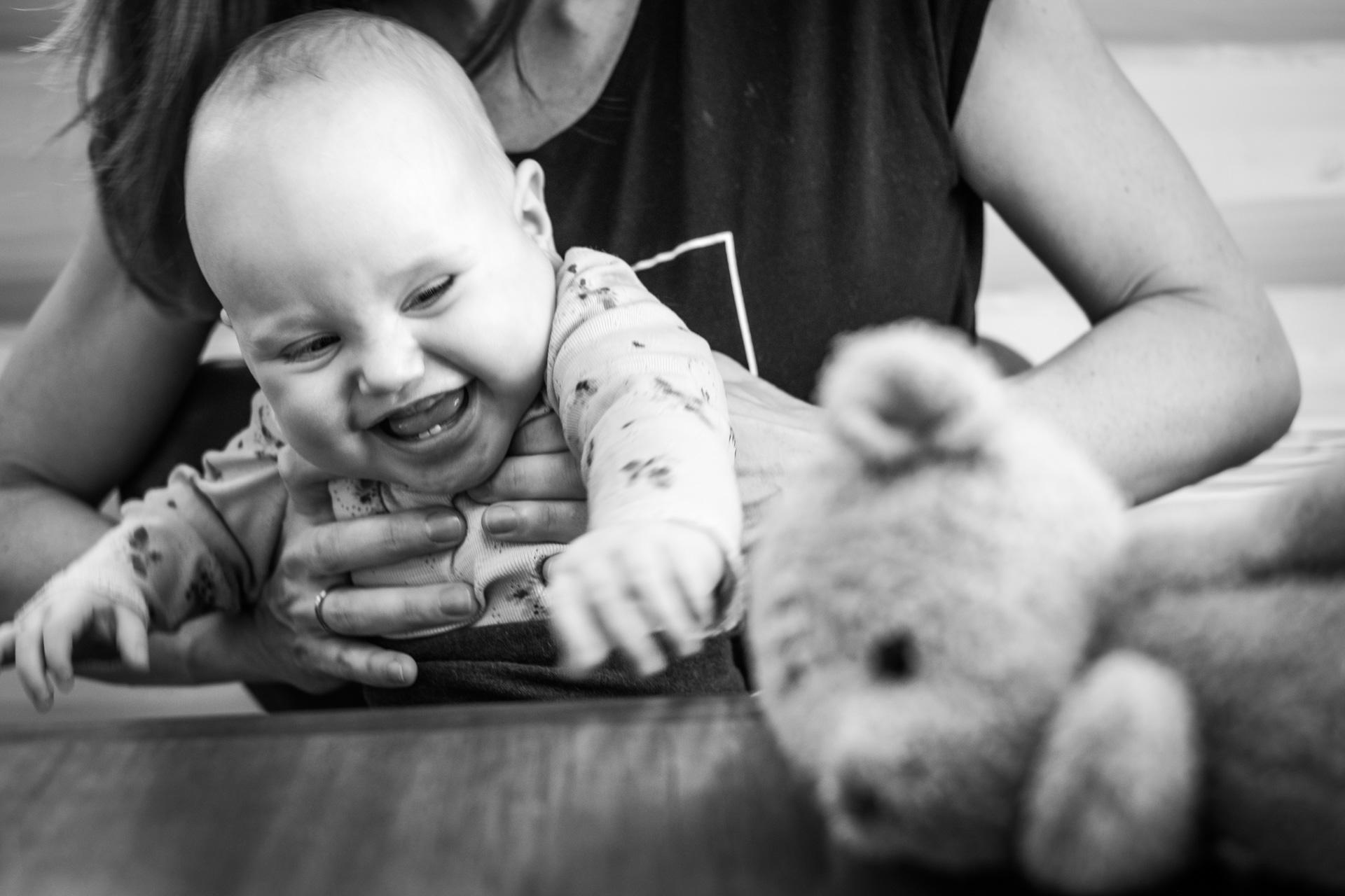 Liten jente sitter i fanget til en voksen. Jenta ler, og strekker seg etter bamse som ligger foran henne.