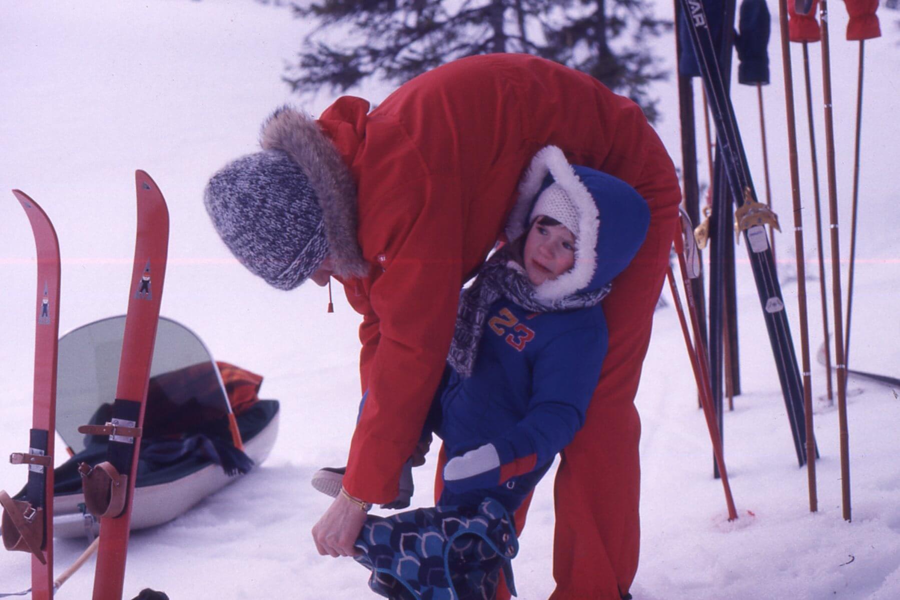 Gammelt fotografi av barn som får hjelp av en voksen til å ta på seg skiene.