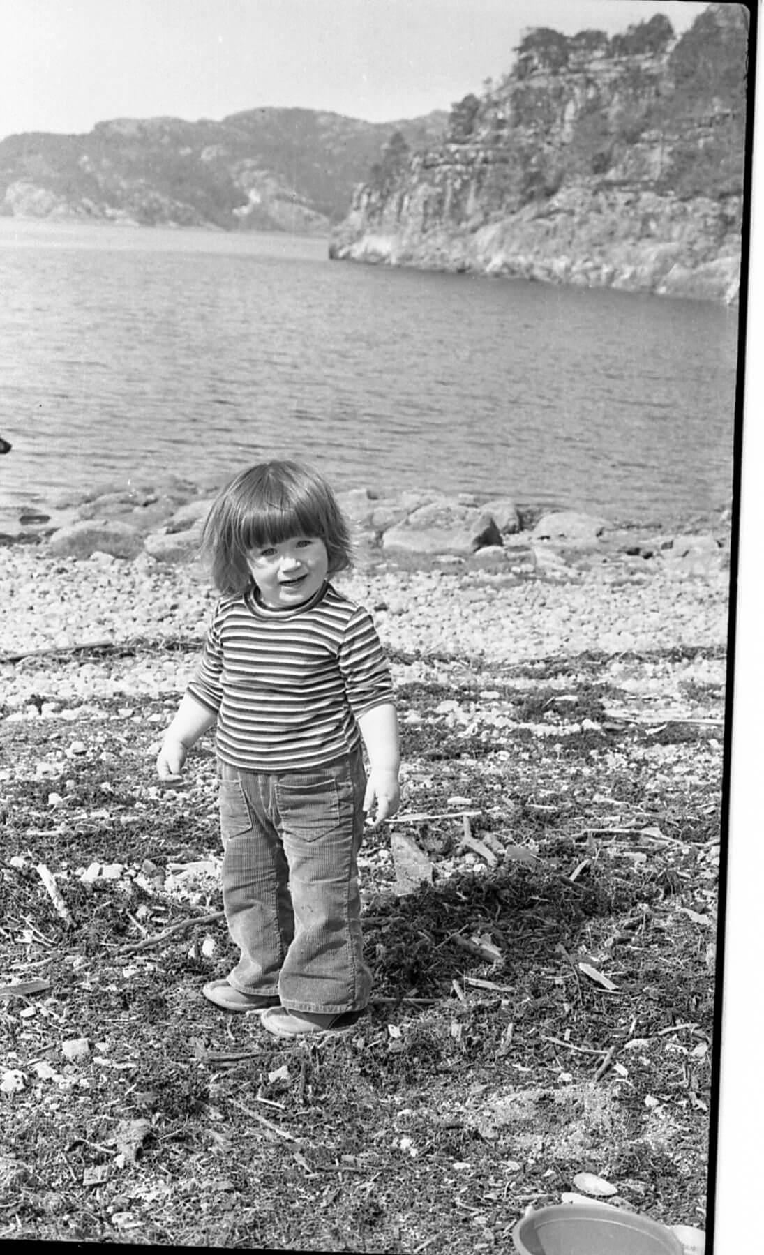 Gammelt fotografi av liten jente som står i fjæresteinene.