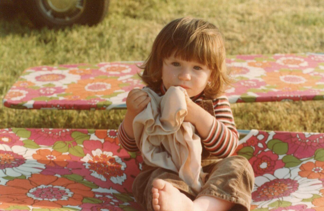 Liten jente på campingtur, sitter på blomstrete solsenger fra 70-tallet