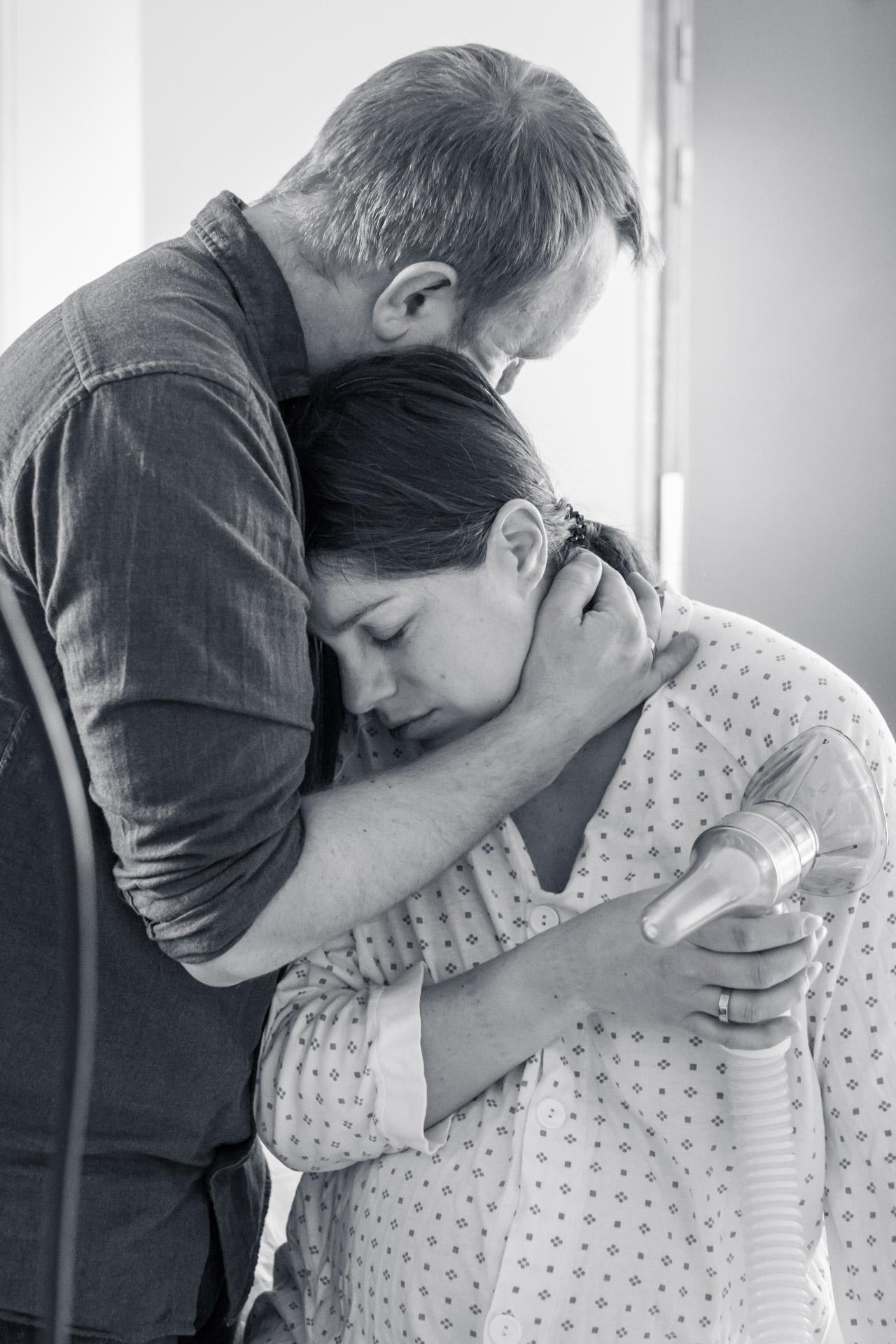 Mann holder omkring sin fødende kone. Hun holder lystgassen i hånda, og hviler hodet mot hans skulder.
