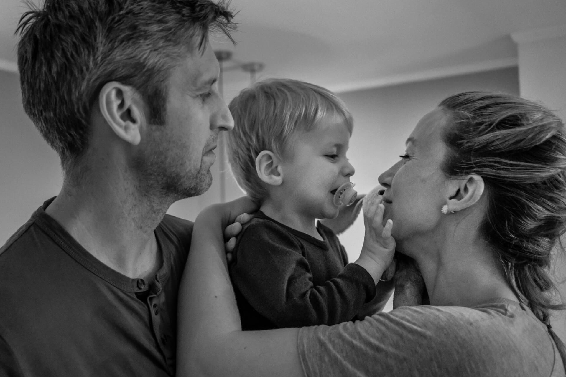Liten gutt med smokk i munnen blir holdt i foreldrenes armer. De smiler og koser med hverandre.