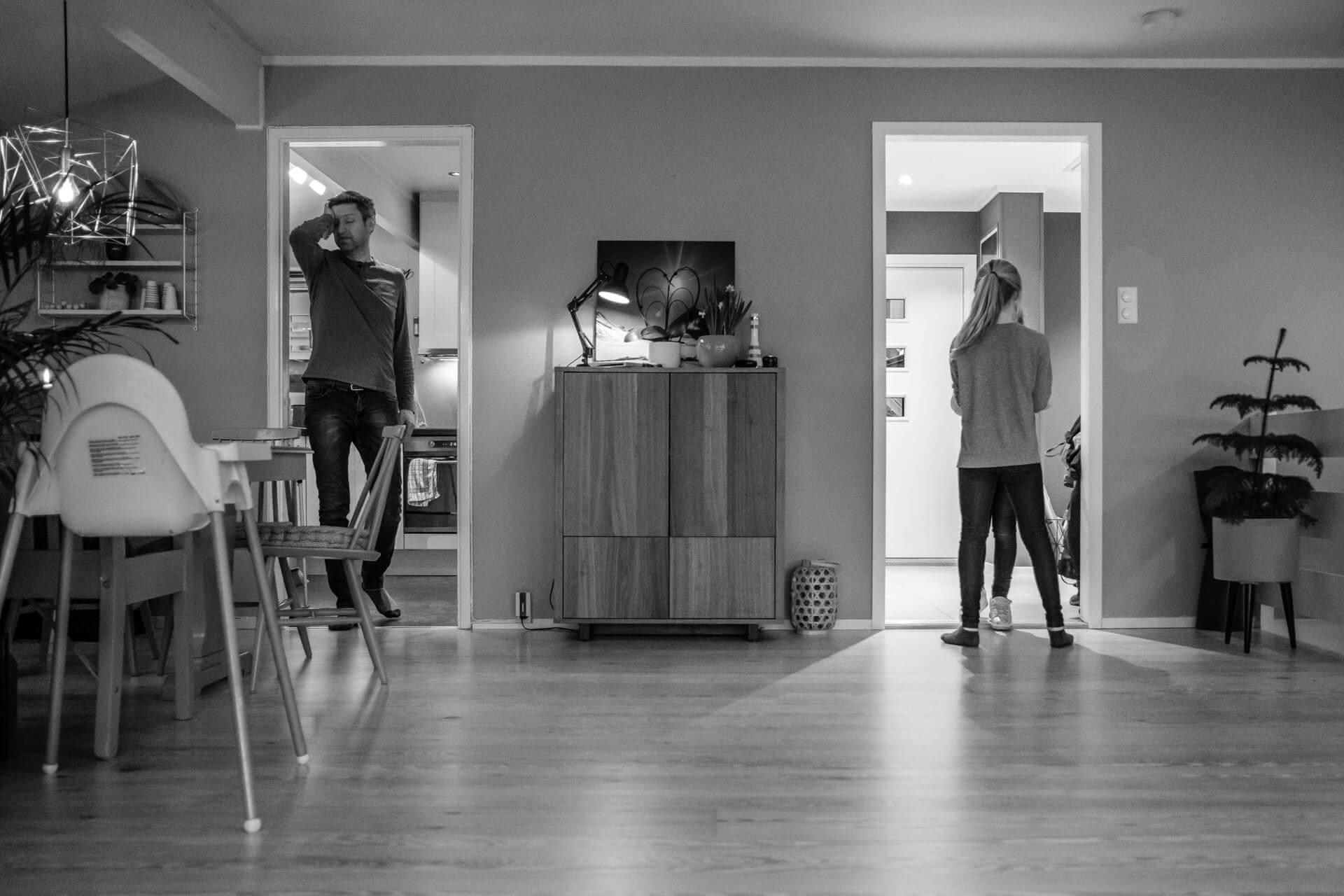 I stua hjemme hos barnefamilie. To barn står med ryggen til i en døråpning, far står i en annen døråpning og ser ganske sliten ut. De ser ikke hverandre.
