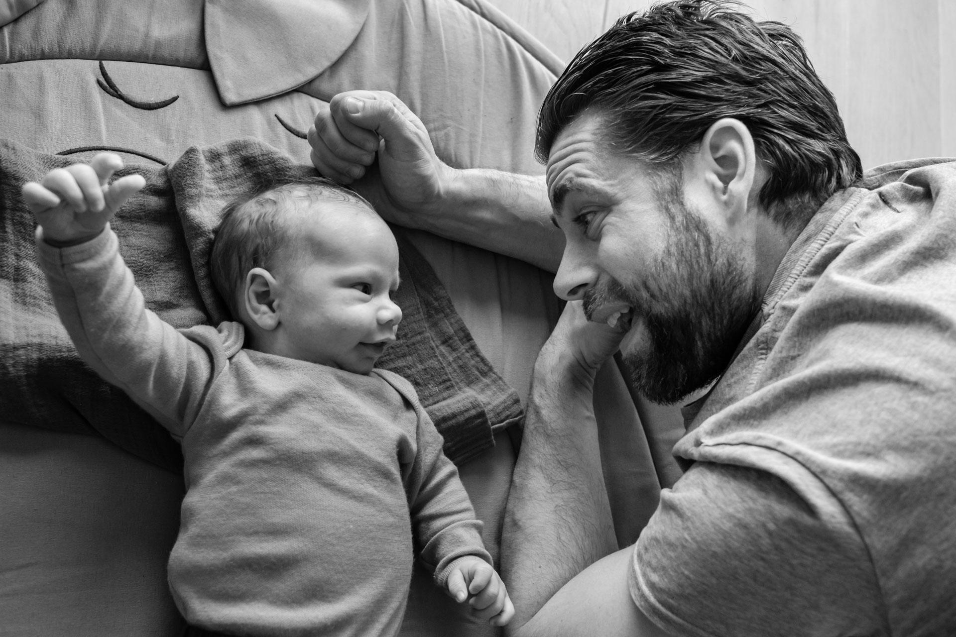 Far ligger på gulvet sammen med sin nyfødte sønn. De ser på hverandre, og vi kan ane et lite smil fra den lille babyen.