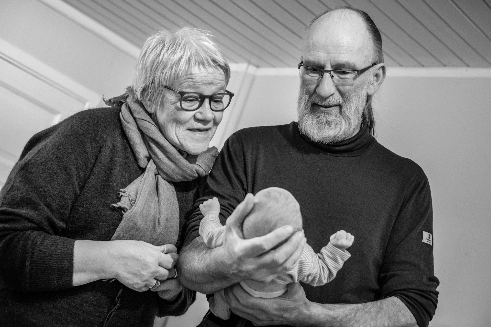 Besteforeldre møter sitt nyfødte barnebarn for første gang. Babyen ligger i bestefars store og trygge hånd, og besteforeldrene ser på og beundrer barnebarnet sitt.