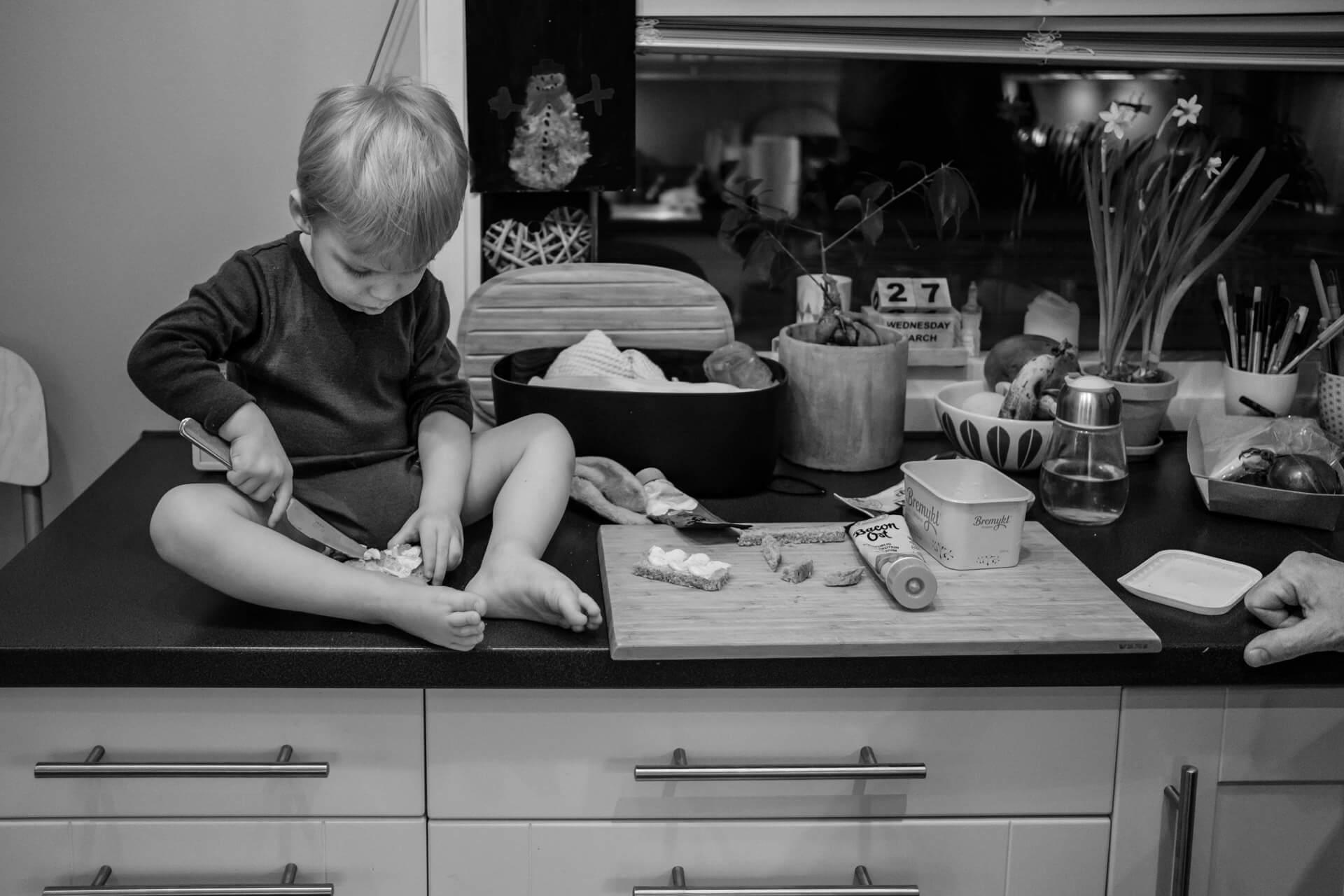 Liten gutt sitter ved siden av brødfjøla oppå kjøkkenbenken, og smører brødskiven sin selv.