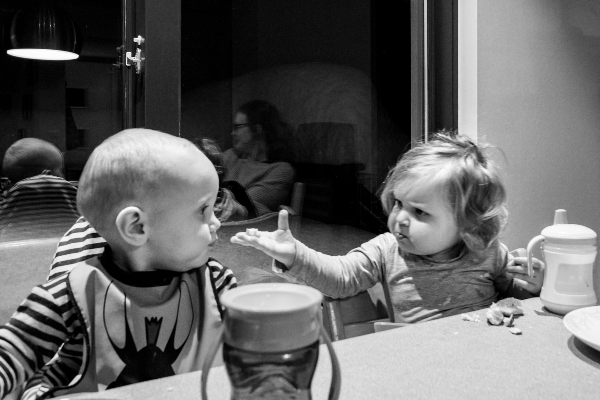To små barn sitter ved spisebordet. De har en tydelig kontakt ved å se på hverandre og med kroppsspråk. På bordet ser vi tutekoppene deres.