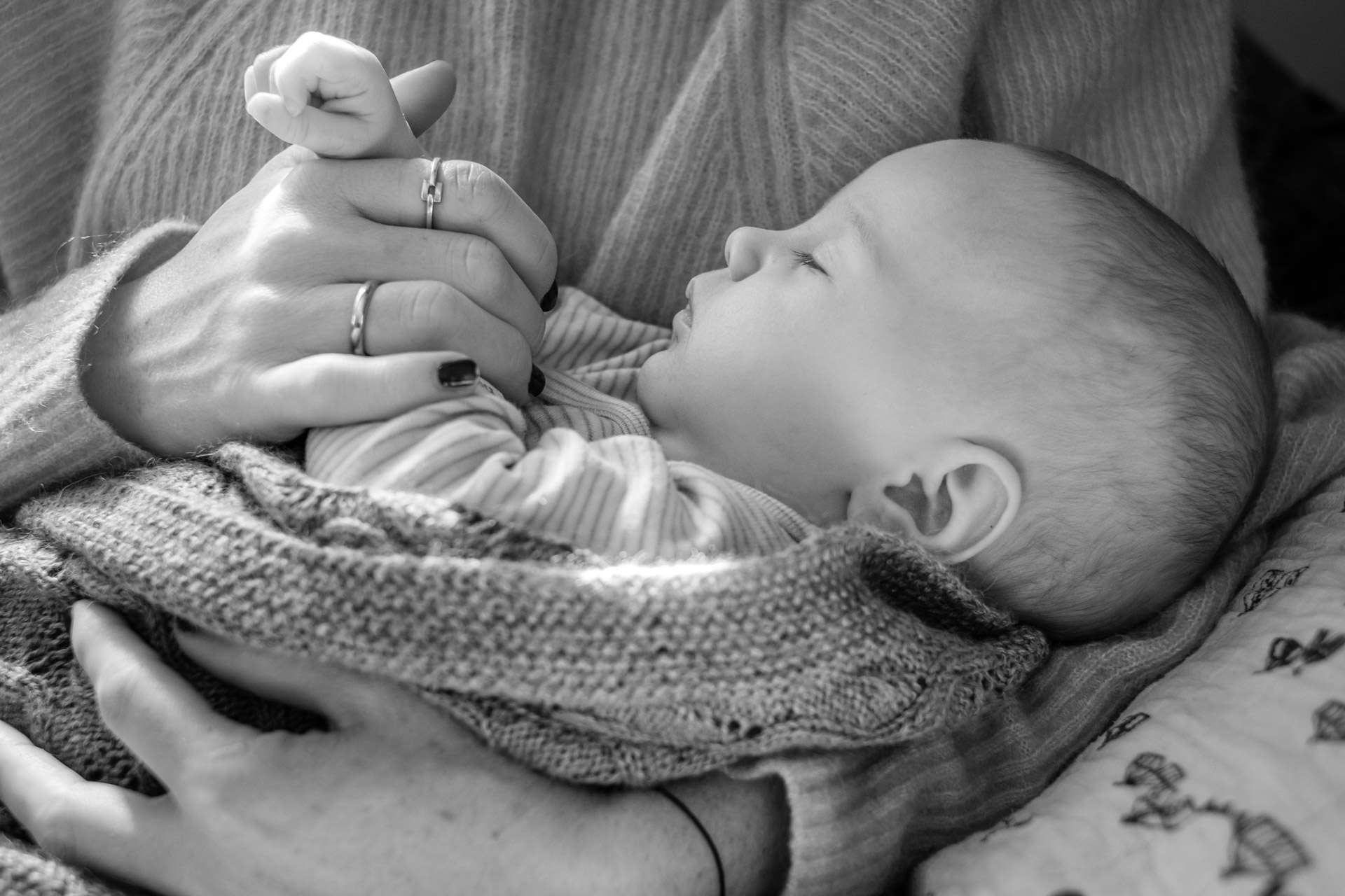 Nyfødt baby ligger i armkroken til en voksen.