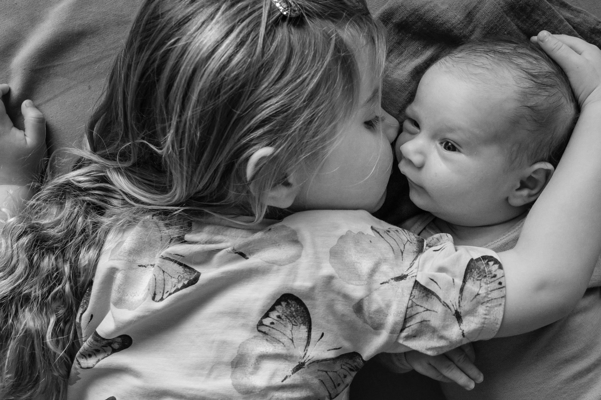 Storesøster ligger på gulvet tett inntil nyfødt baby, og holder forsiktig omkring ham.