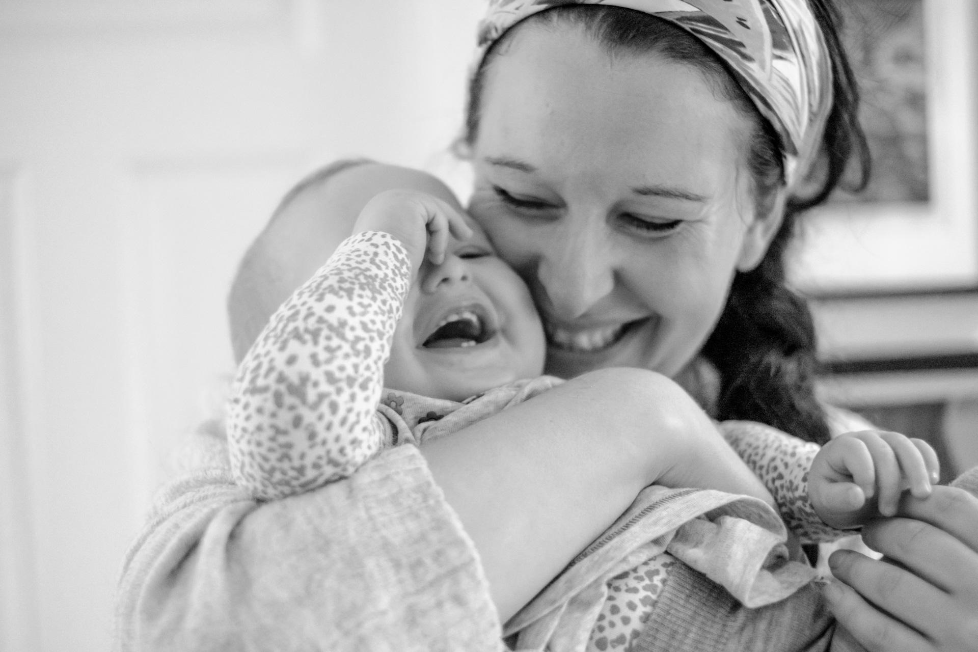 Mor og datter smiler og ler, mor holder datter i armene og gir henne en god klem.