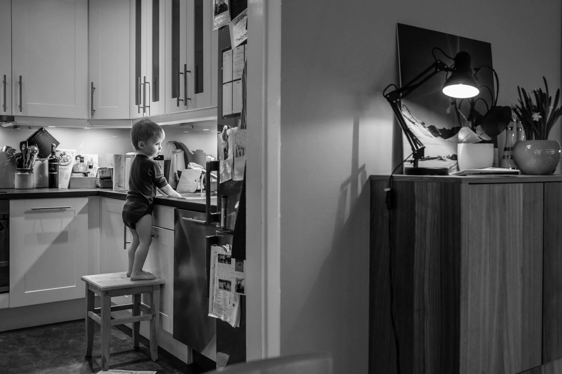 Liten gutt står oppå en krakk ved kjøkkenbenken. Det ser ut som han er helt alene, og han ser tenksom ut.