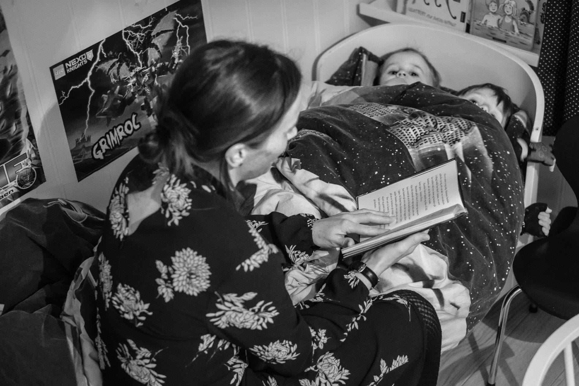 To små gutter ligger i senga, under samme dyne. Mor sitter på sengekanten og leser bok for dem.