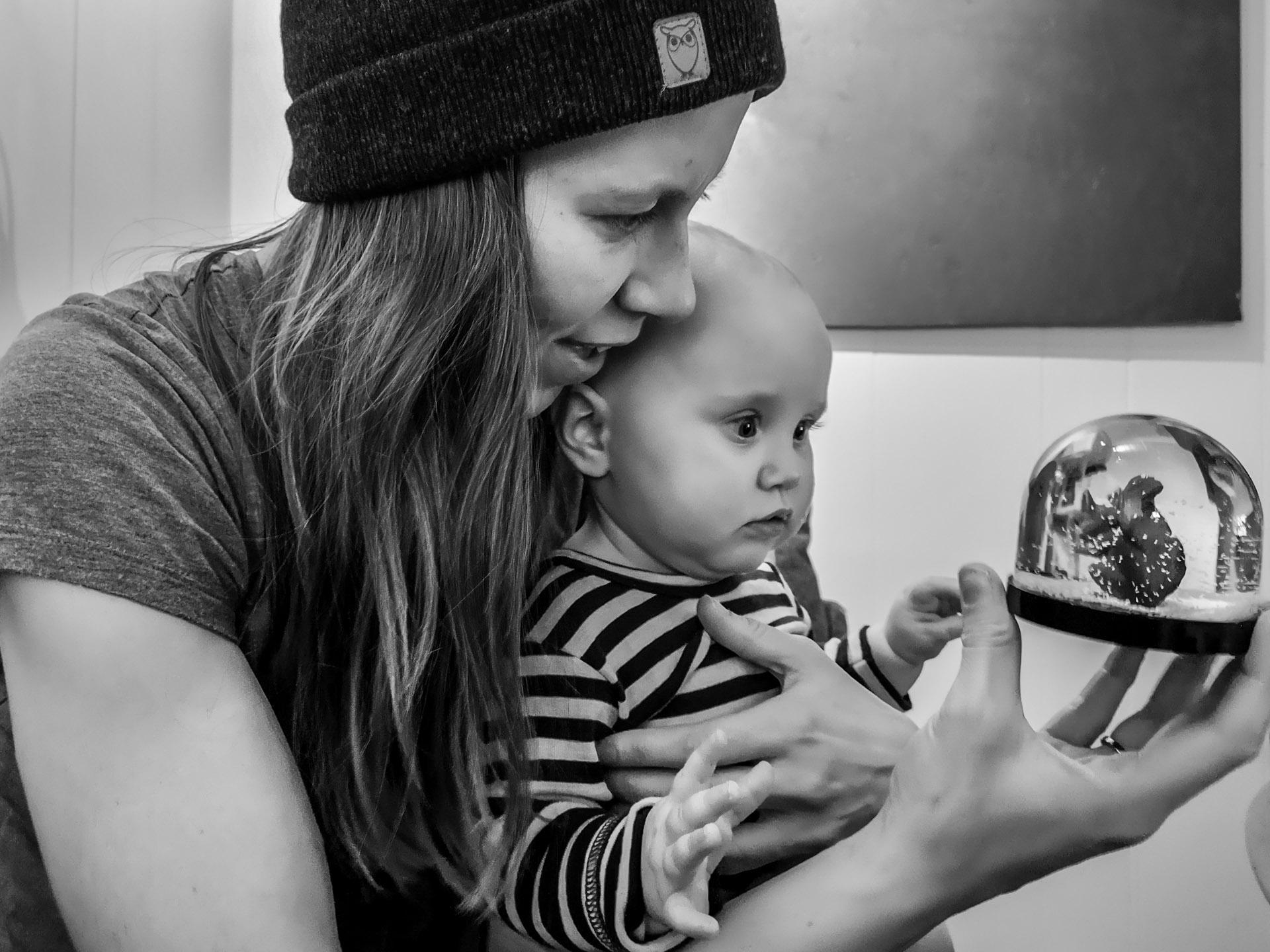 Mor sitter med liten datter på fanget, og de ser begge interessert på en leke som mor holder i hånden.