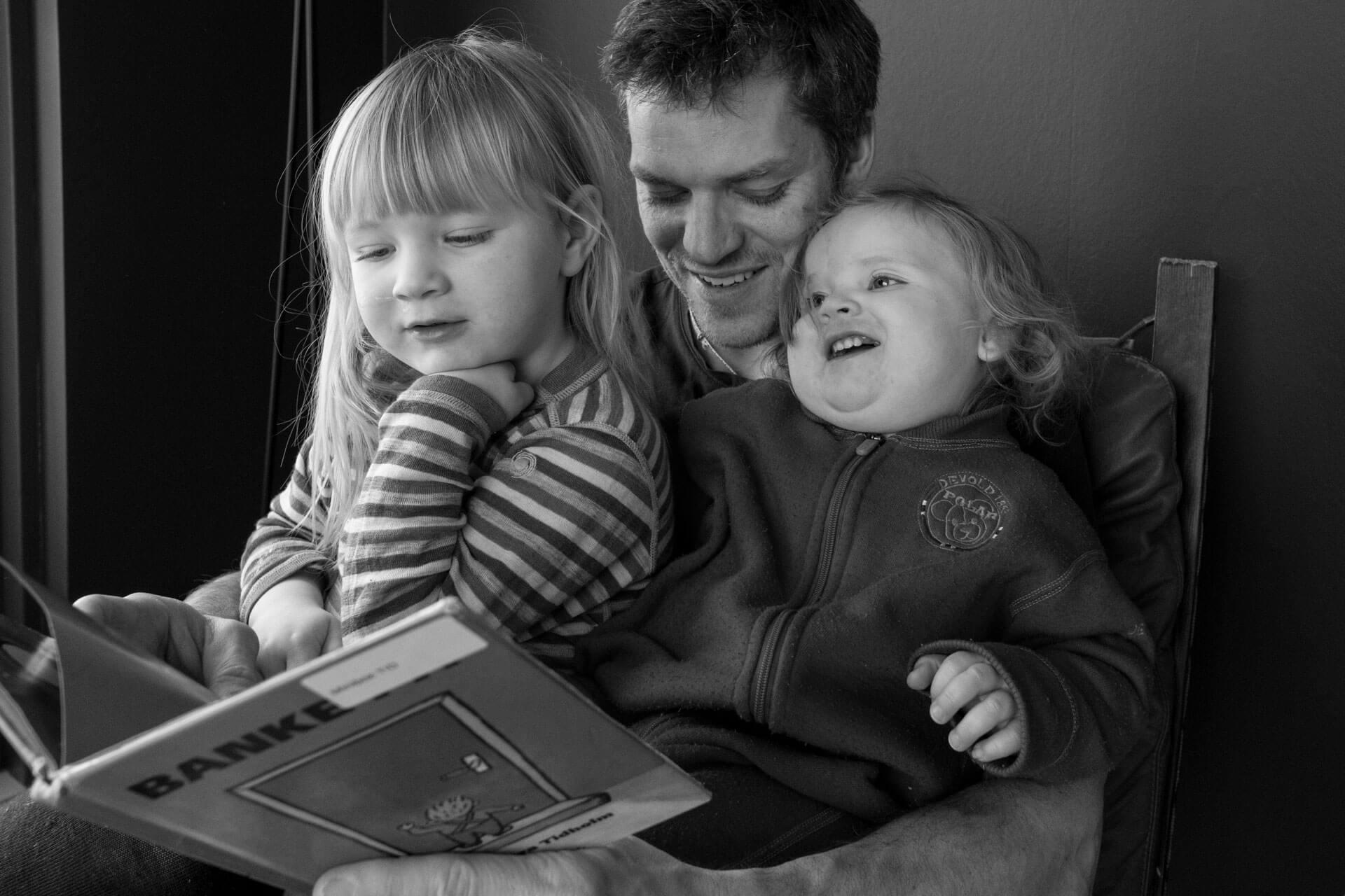 To små barn sitter på pappas fang mens de leser bok.