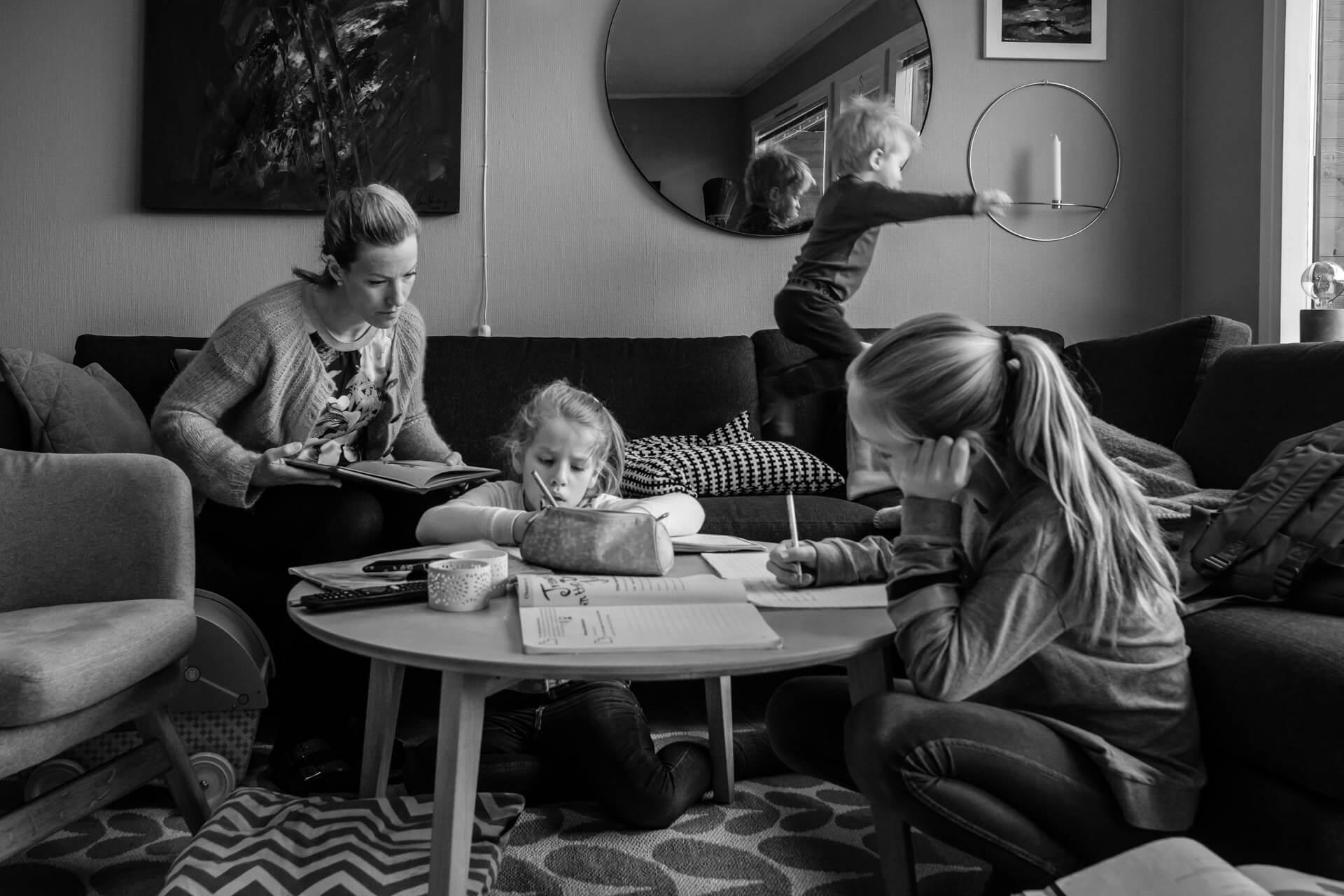 En barnefamilie er samlet rundt stuebordet. Mamma hjelper de to eldste jentene med leksene, mens lillebror hopper i sofaen.