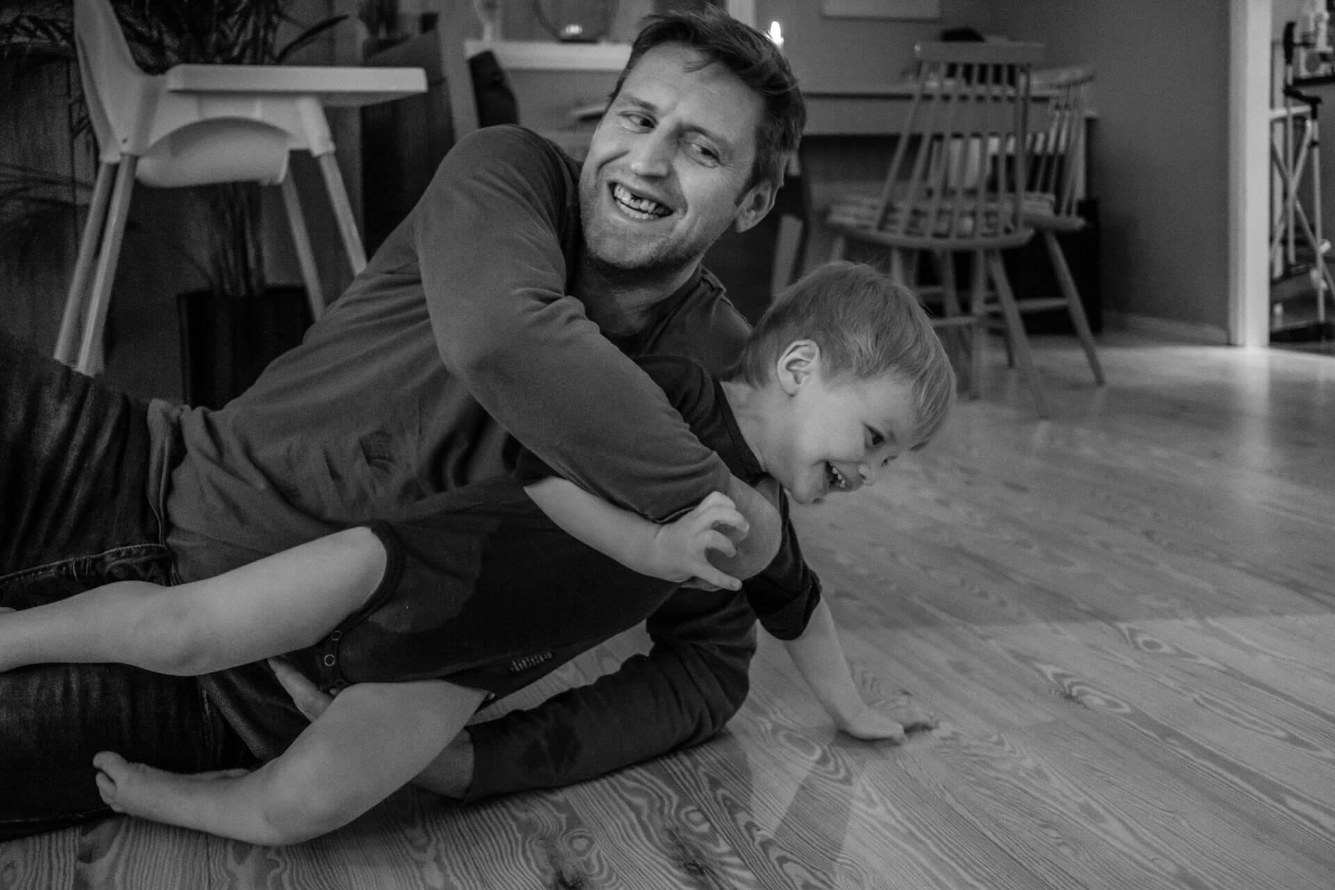 Far og sønn leker på gulvet. Far holder omkring den lille gutten og herjer med ham. De smiler og har det tydeligvis gøy.