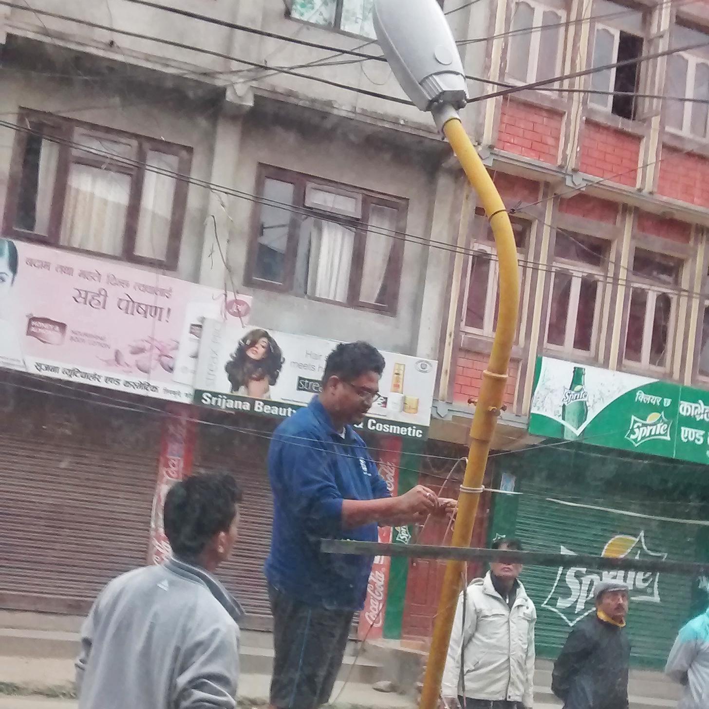 SunFarmer engineers Avi and Kushal fixing a solar lamp to give a Kathmandu street light after sundown
