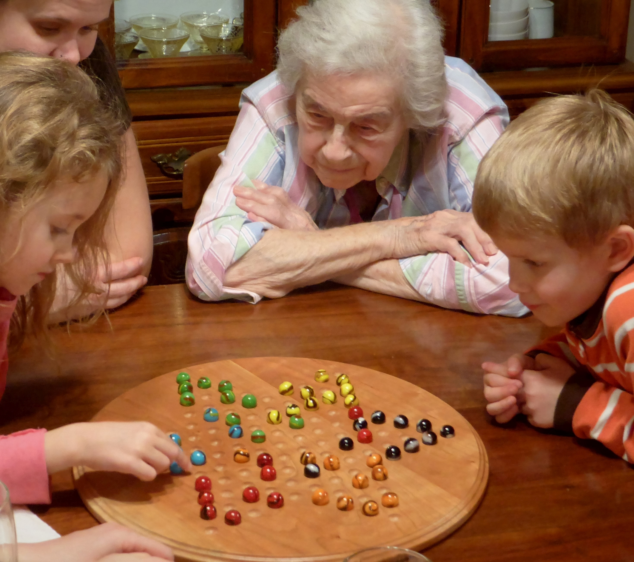 Three generations gathered around our handmade Chinese checkers board.