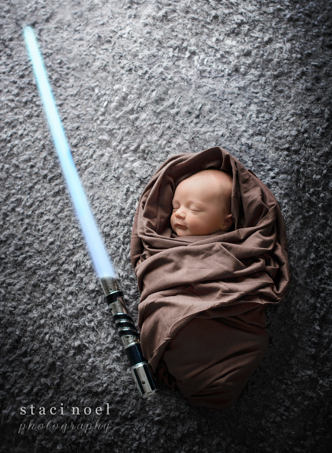 Concord, NC newborn baby boy photographed by Staci Noel Photography as a Star Wars Jedi with light saber on grey backdrop