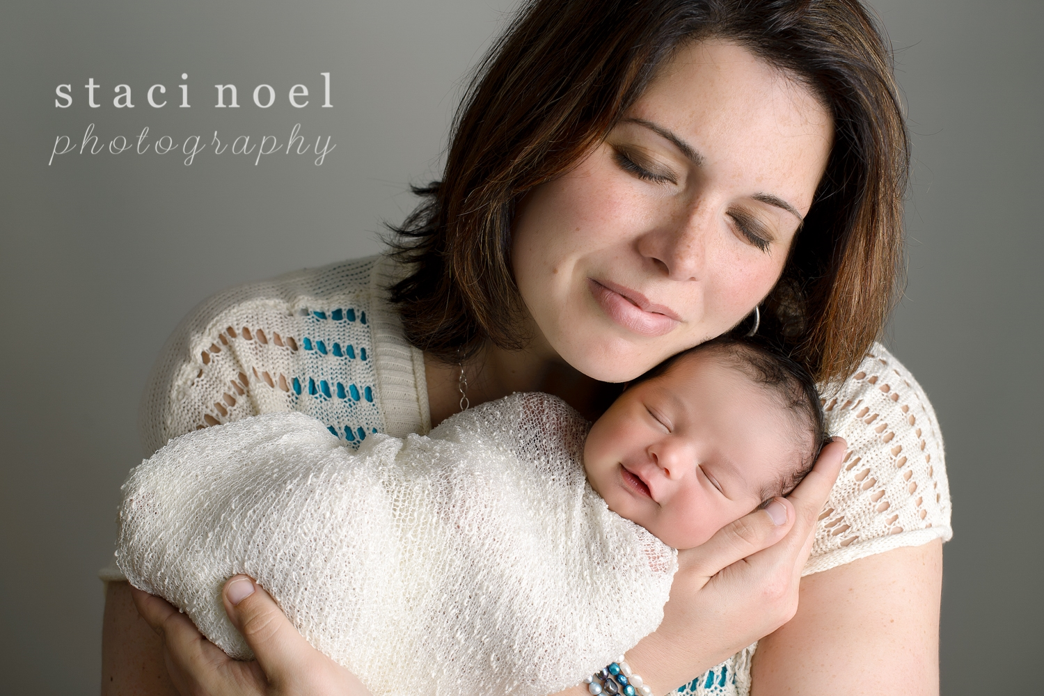 Harrisburg NC newborn baby girl photographed in her mothers arms smiling on a grey wall by Staci Noel Photography